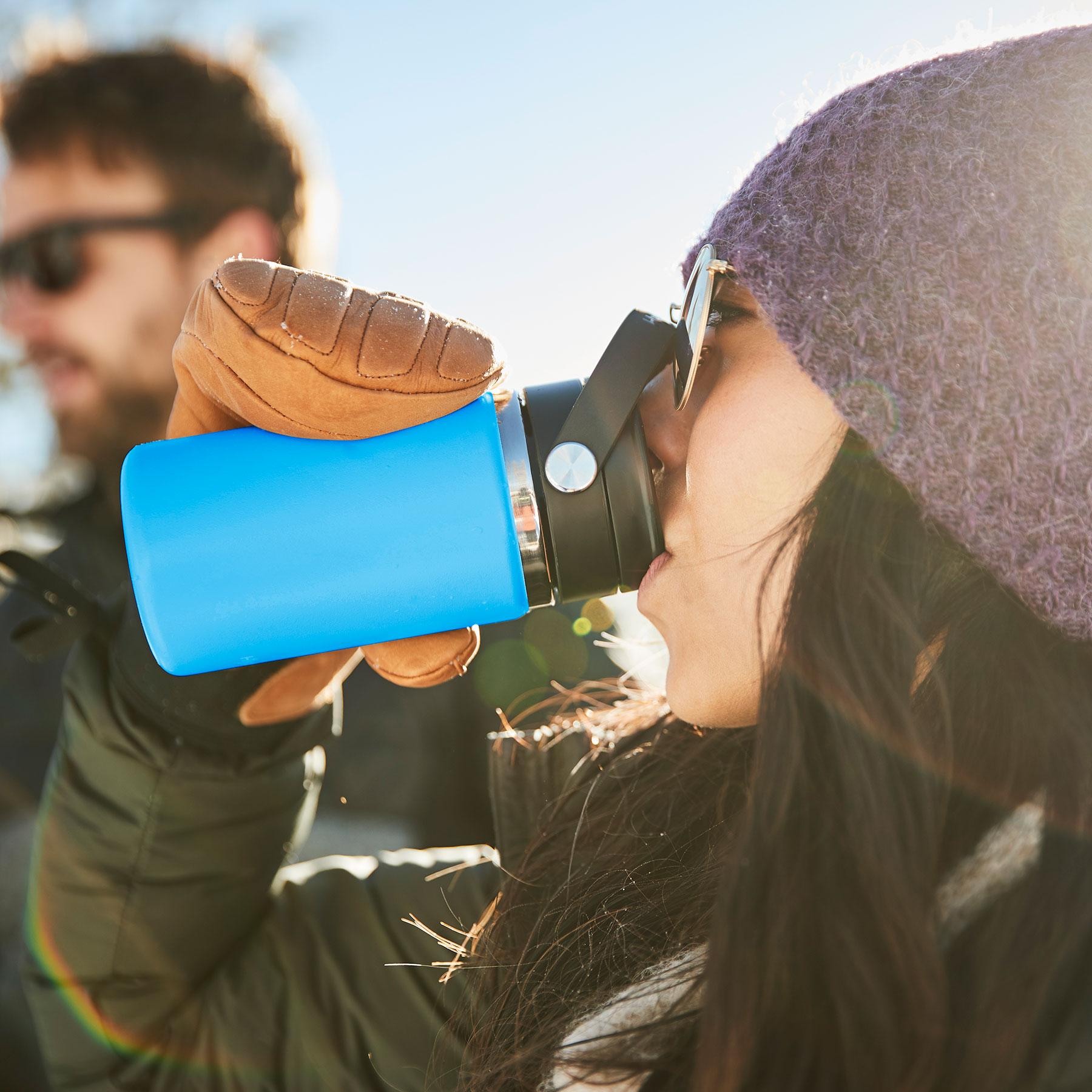 Ein Mädchen trinkt einen Schluck aus ihrem Kaffeebecher mit Flex Sip.
